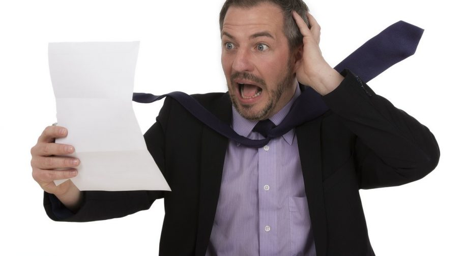 Businessman looks in shock at a document he just read