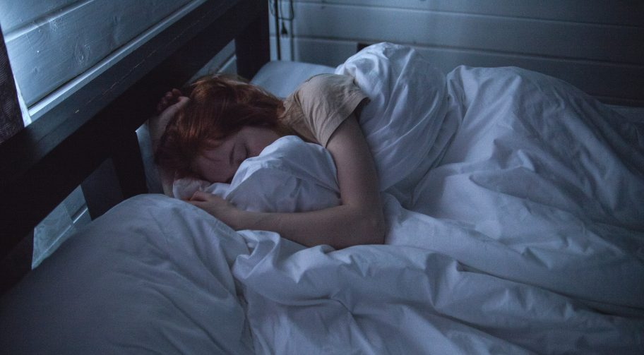 Woman asleep in a darkened room in a comfy bed