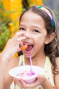 Little girl eating carrot while holding a bowl of ice cream. Photo by Patricia Prudente on Unsplash